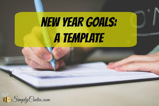 A person writes their new year's goals on a journal
