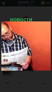 мужчина читает газету и видит новости в ней