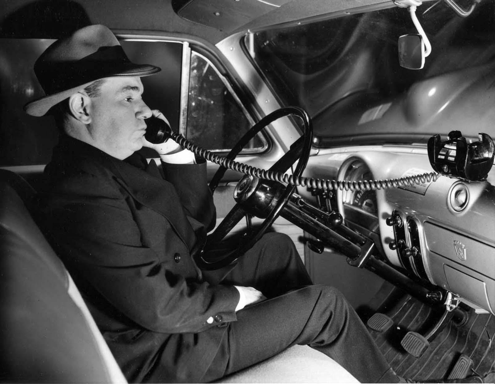 Um homem usando um telefone celular em um automóvel. 1954