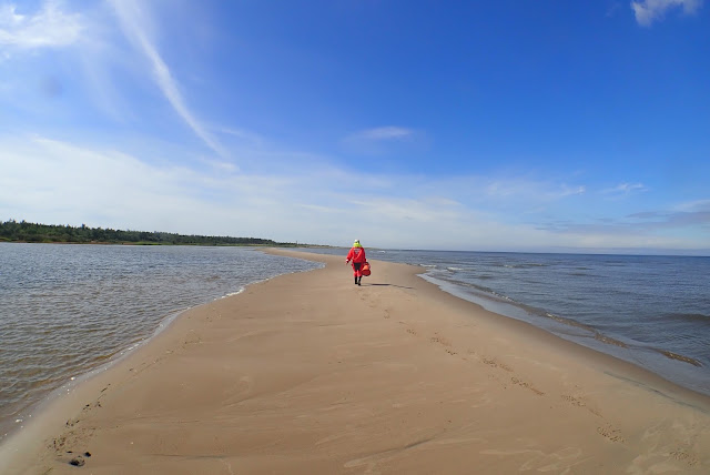 A person walking on a sand bank on sunny day.