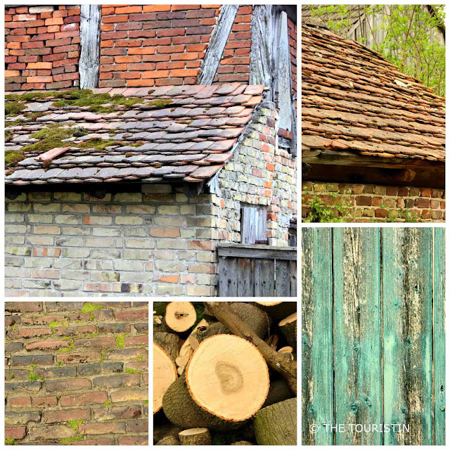 Rustic red-tiled roofs and a weathered green door of a barn.