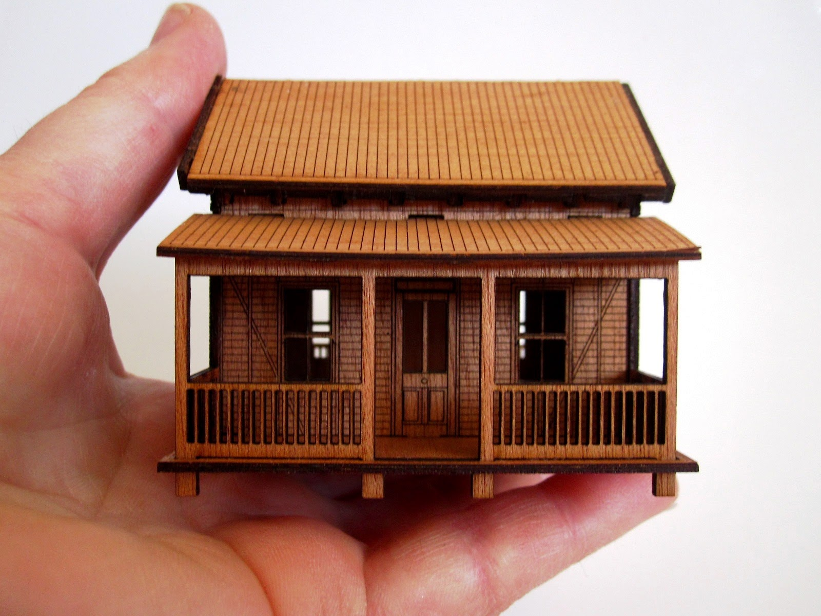 Wooden laser-cut miniature wooden cottage, held by a hand.