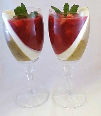 Unas copas con capas inclinadas de kiwi, fresas y yogur griego
