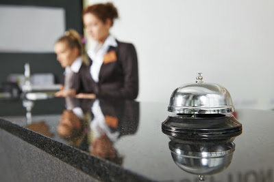 Photo of a hotel front desk with a bell for attention in the foreground