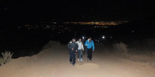 Tres personas ascendiendo cerro durante la noche