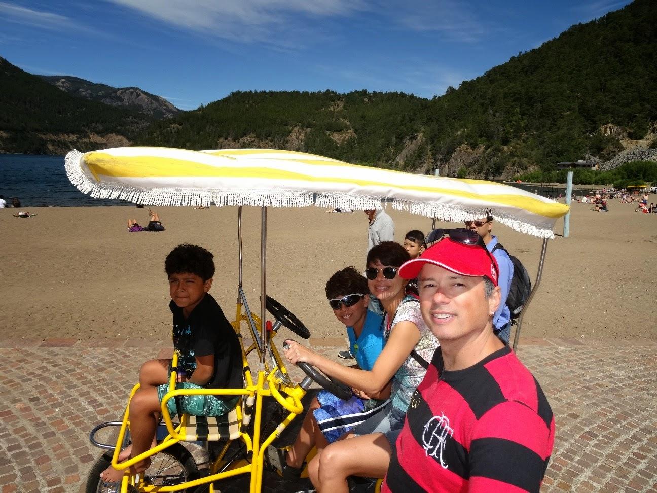 Família andando de bicicleta no calçadão em frente à praia