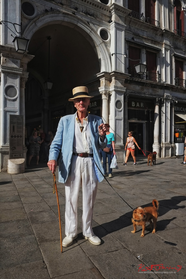 Classic Italian menswear for summer, panama hat, linen jacket and trousers, a cane, a dog and a cigar. Piazza San Marco, Venice. Photographed for Street Fashion Sydney by Kent Johnson.