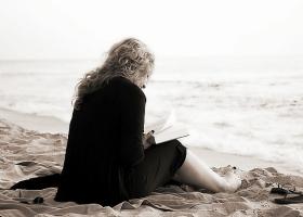 A girl reading a book on a beach.
