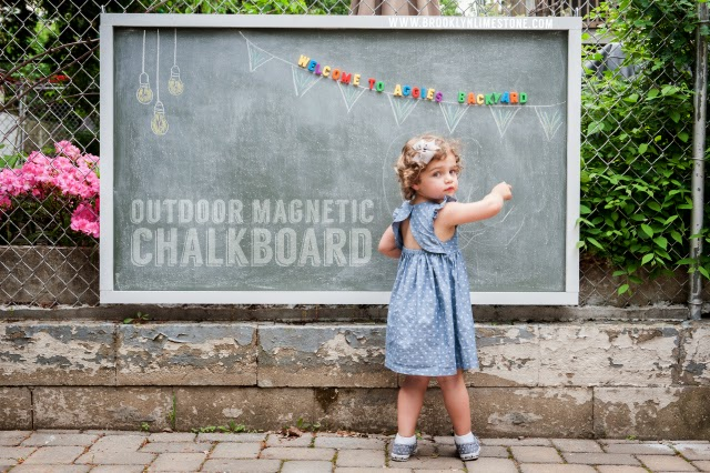 Daughter Aggie looking over her shoulder in front of the magnetic outdoor chalkboard that has magnetic letters spelling Welcome to Aggies Backyard over a chalk drawn banner