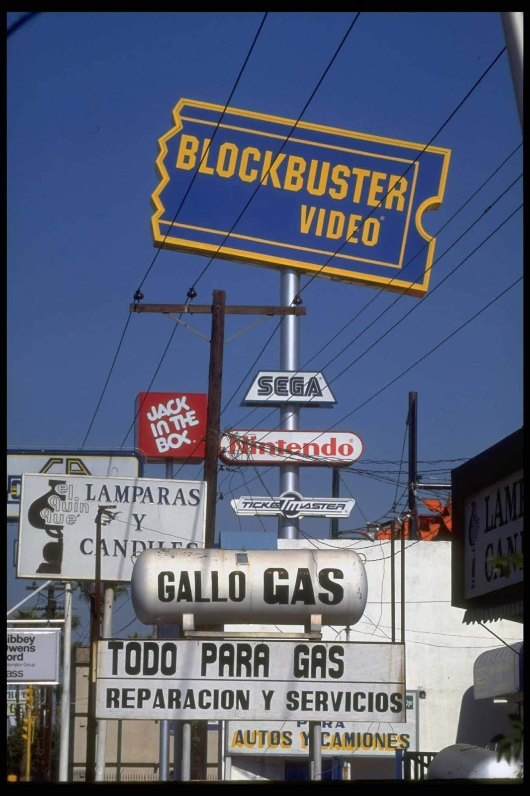 Blockbuster Video store & Jack In The Box fast food eatery among Amer. & Mexican services & products advertised on street signs in border town.