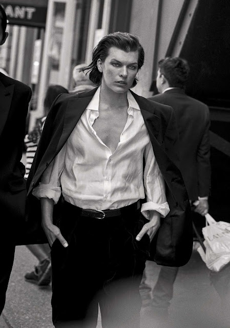 Actress Milla Jovovich looking stern, wearing a white shirt and suit coat.