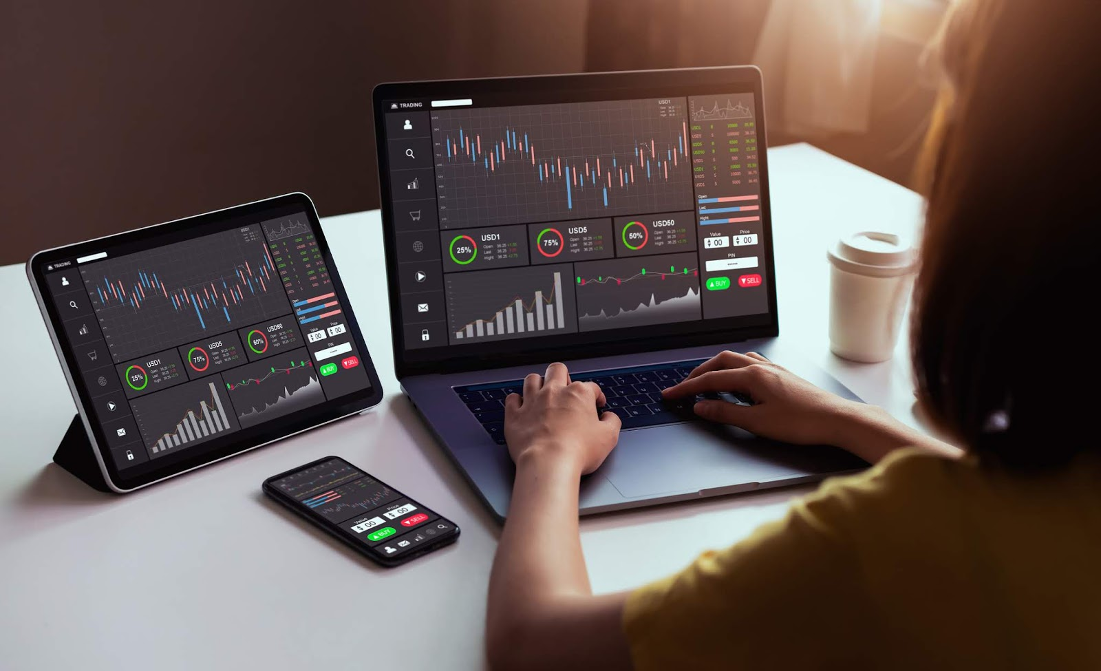 Trader trading on a laptop and also using tablet and mobile online trading platforms