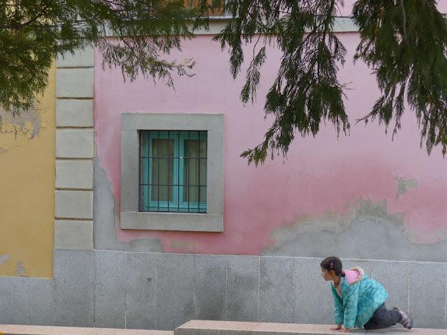 Fachada rosa con niña agachada