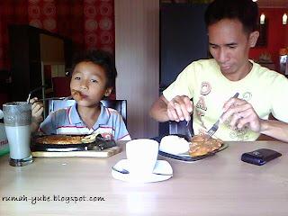 bapak dan anak sedang makan asik