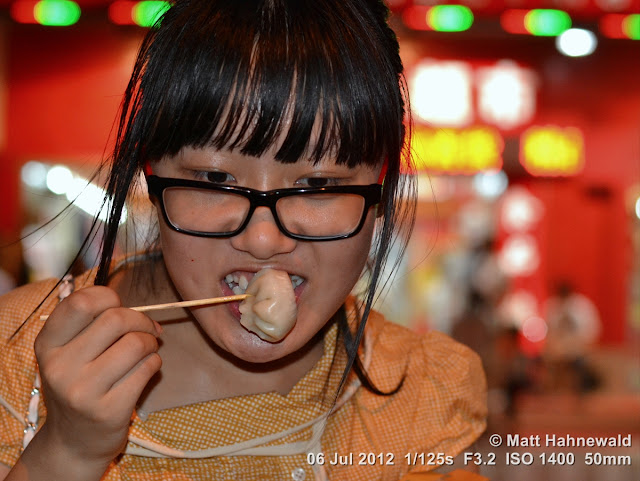 China, Beijing, Donghuamen night market, Chinese food delicacies, portrait, Chinese girl eating steamed dumplings, jiaozi