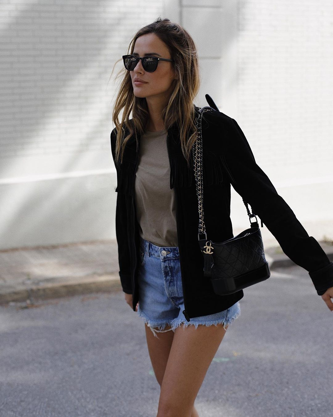 How to Transition Cutoff Shorts Into Fall — Alex Rivière in a black jacket, neutral t-shirt, and classic Chanel chain strap bag