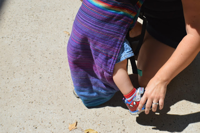 Image of fair skin woman guiding fair skin baby's legs into the shoulder straps of purple rainbow handwoven Onbu