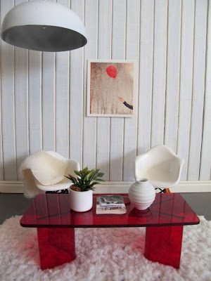 Modern one-twelfth scale miniature lounge scene with concrete floor, white panelled walls, white Eames chairs and a red perspex coffee table.