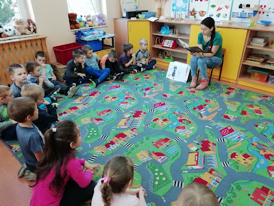 Dzieci siedzą w półkole i słuchają bibliotekarki
