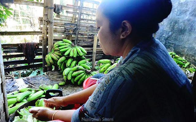 Seorang ibu mengupas pisang untuk dijadikan kripik