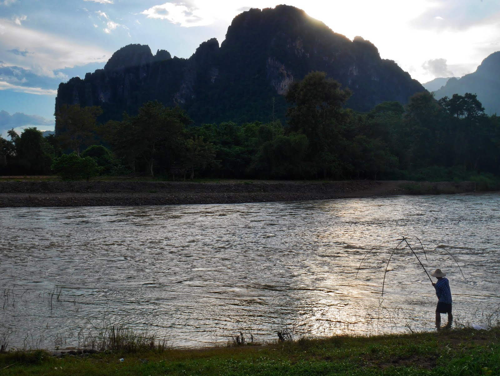 a local fisherman catching fish with a net as the sun sets over the river with the mountains in the background, vang vieng, laos