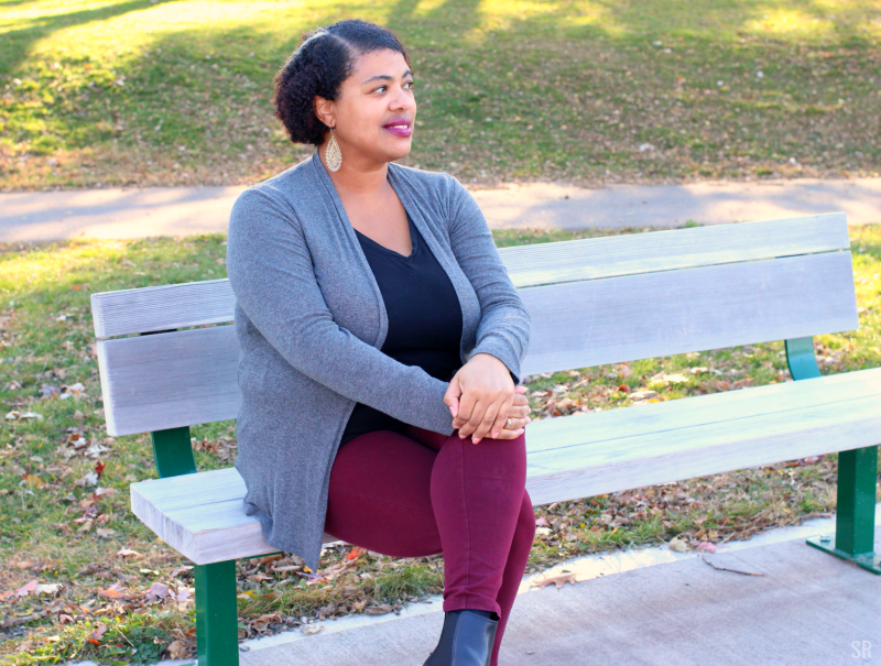 a black woman sitting on a park bench