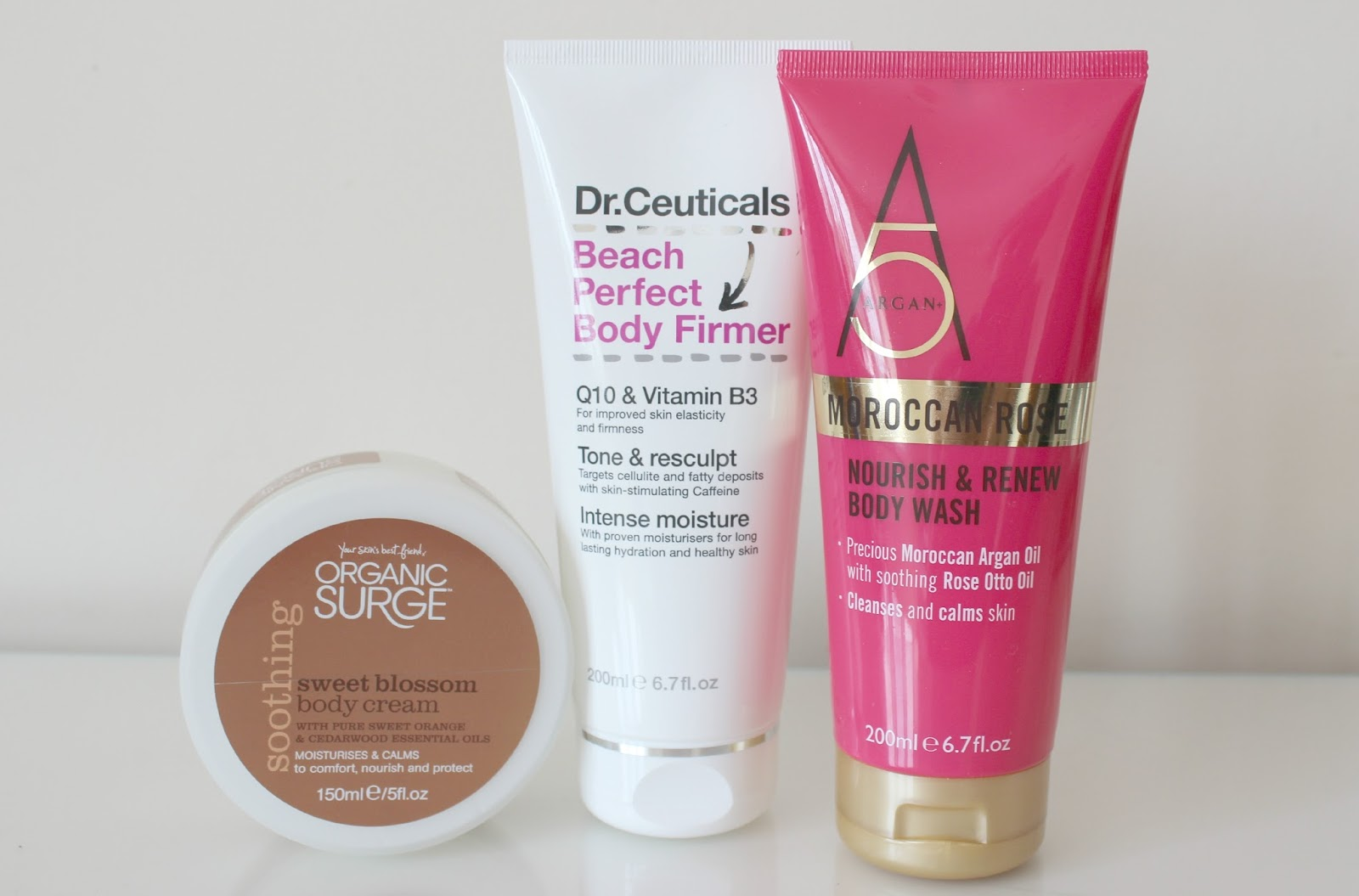 A picture of Dr. Ceuticals Beach Perfect Body Firmer, Organic Surge Soothing Sweet Blossom Body Cream and Argan+ 5 Moroccan Rose Nourish & Renew Body Wash.