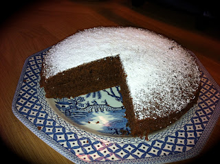 Wheat Free Chocolate Cake on a plate, with a large slice missing!