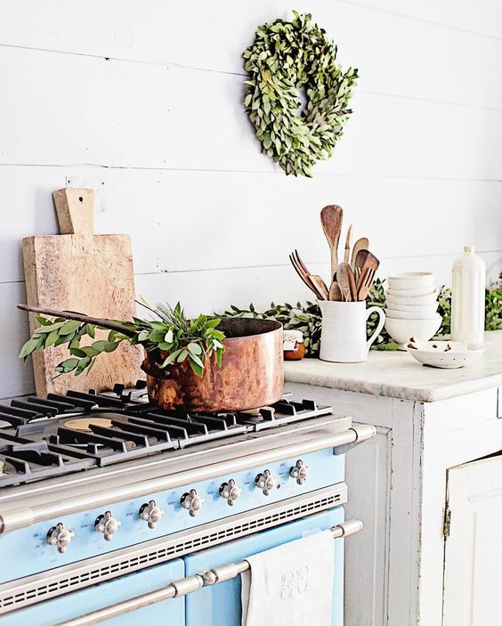 Dreamywhites kitchen with blue range, copper pot, and natural greenery