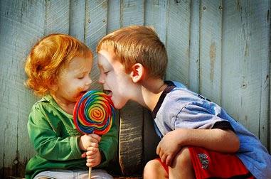 Niño y niña compartiendo una chupeta