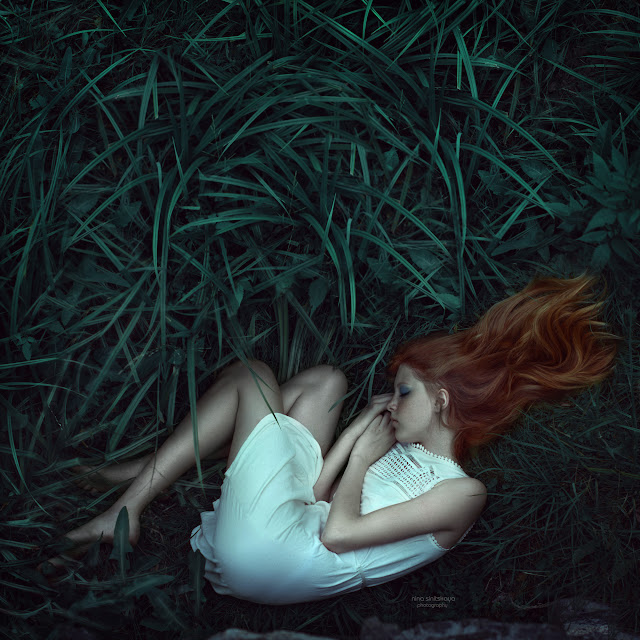 Young girl with red hair, freckles and pale skin lays down on the green grass and sleep