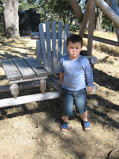 Leo, a preschool-age white boy, next to an outdoor picnic table set