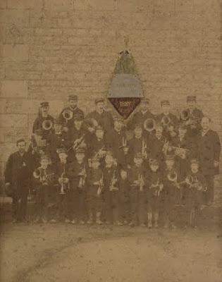Première photographie de la Fanfare des Ecoles Laïques-les Amis Réunis, prise à Montceau en 1887, devant l'école de la rue de l'Est, actuel musée (collection particulière)