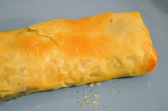 A close up of a strudel with spinach and cheese inside.