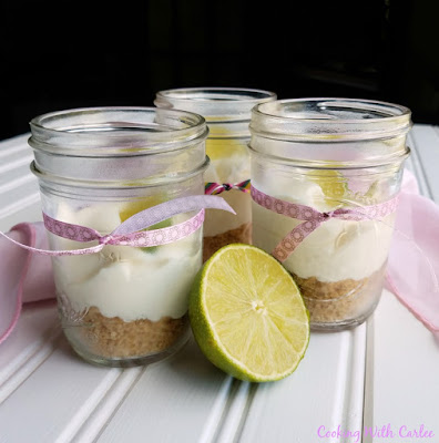 jars filled with key lime pie cheesecake mixture with ribbons and a lime