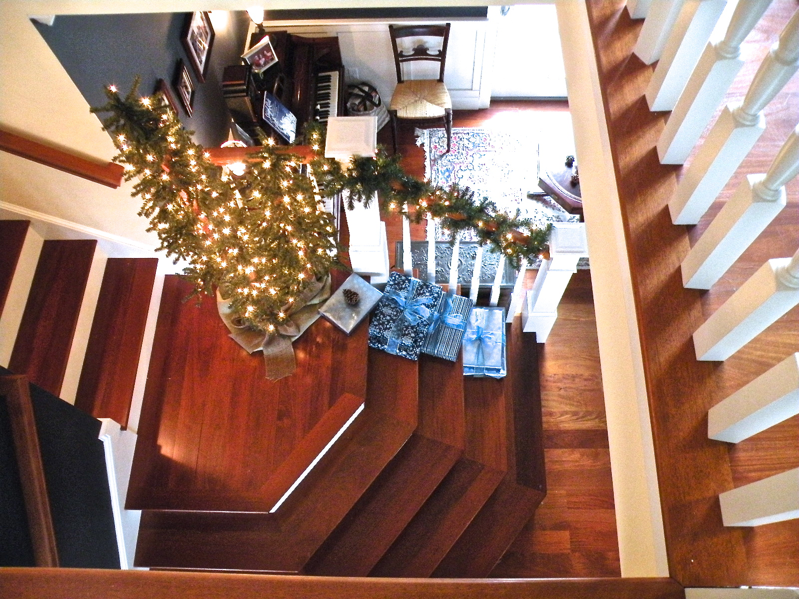 Staircase with lit Christmas tree, blue wrapped packages, Coastal Christmas