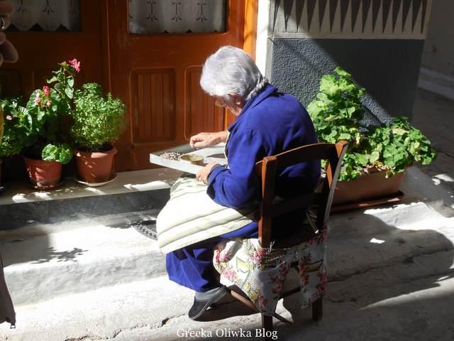 kobieta ubrana na niebiesko trzyma w ręku blaszaną tacę przebiera mastichę