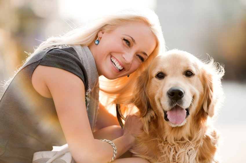 Happy woman laughing with her Golden Retriever panting and looking straight at the camera