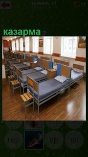 большое помещение в котором стоят в ряд кровати, казарма для военных