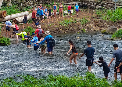 Line of hikers crossing a river using a rope bridge