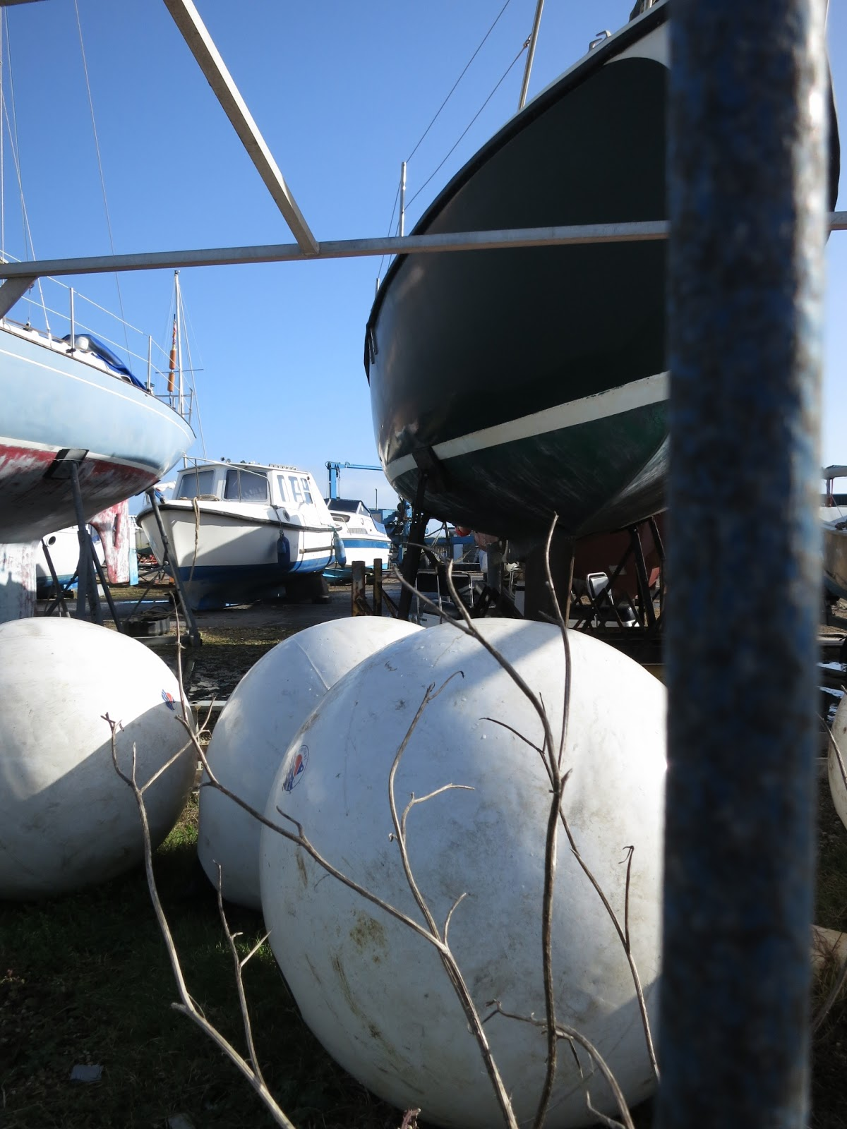 Three large white balls and boats on land in a boatyard