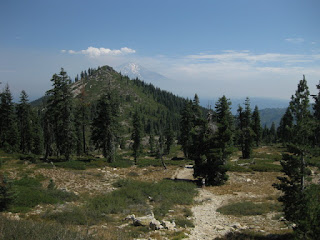 Hiker on rocky trail through a meadow, with Mt. Shasta in the distance, on the way to Heart Lake, Mt. Shasta, California