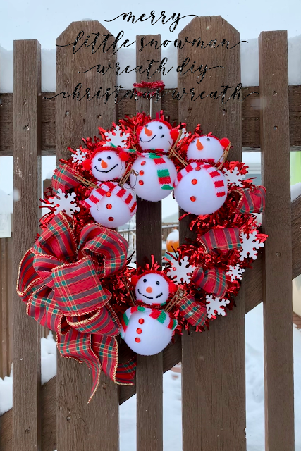 Bright red wreath with cute snowmen ornaments hanging on a wooden garden gate.