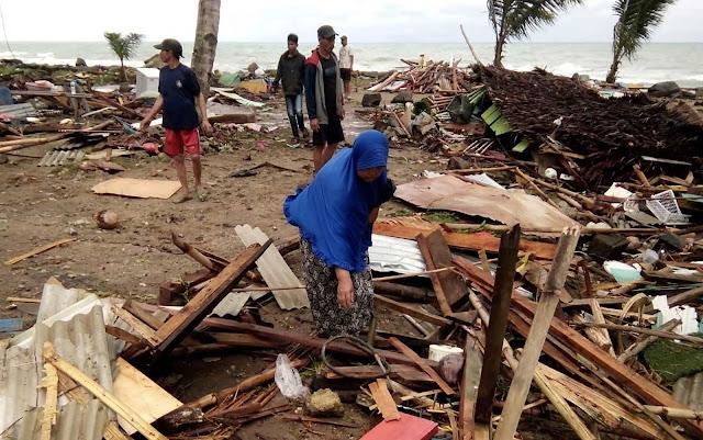 Mulher procurando em meio aos destroços
