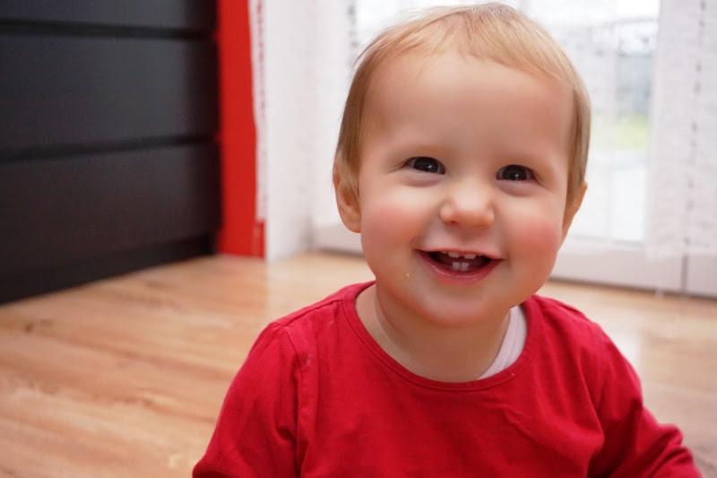 roczniak dziewczynka uśmiech z kilkoma ząbkami