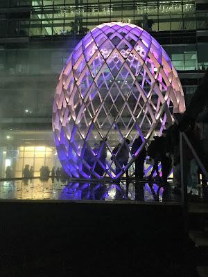 Pic of the huge, skeletal,  egg-shaped installation lit in purple