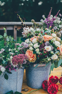 Two metal buckets filled with a variety of multi-colored flowers. Photo by Annie Spratt on Unsplash.
