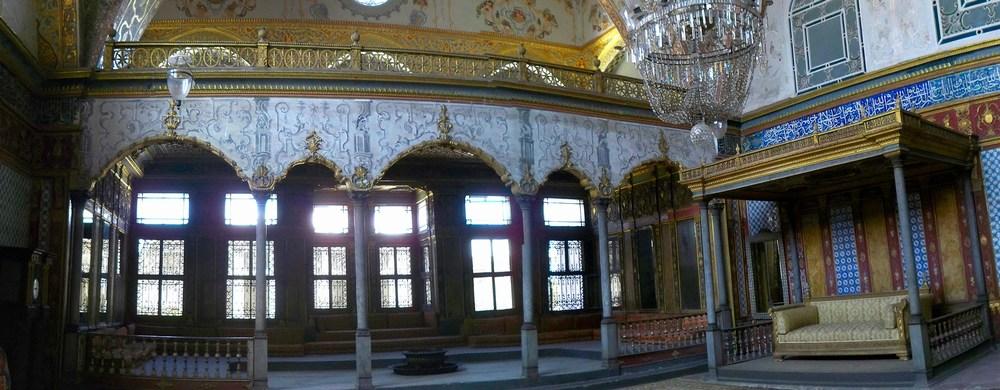 Vue générale de la salle Impériale. Le trône du sultan est au centre. Ce dernier pénétrait dans la pièce par une porte secrète dissimulée derrière le grand miroir que l'on aperçoit à gauche du trône. La galerie en arrière plan, elle, était occupée par ses invités, dirigés par la Mère.