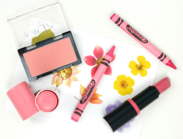pink blusher in a rectangular pan, a black lipstick tube with pink band around it, and pink cream blusher in a tube