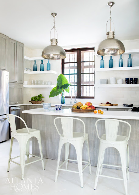 White modern farmhouse kitchen with open shelves, Tolix stools, shiny dome pendant lights, and blue bottles